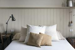 Double bed with pillows and cushions Stock Photos