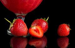Cropped view of strawberries with goblet on black background - stock photo