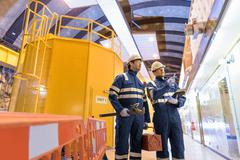 Workers in generating hall in hydroelectric power station Stock Photos