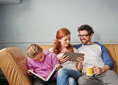 Mid adult parents and daughter on sofa on reading book and digital tablet Kuvituskuvat