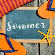 flip-flops, starfish and text sommer, summer in German - stock photo