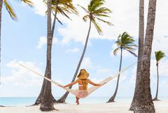 Rear view of young woman sitting on beach hammock, Dominican Republic, The Stock Photos