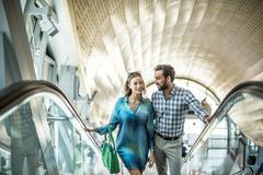 Tourist couple moving up shopping mall escalator, Dubai, United Arab Emirates Stock Photos