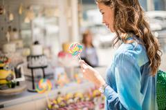 Woman with lollipop from sweet stall, Dubai, United Arab Emirates Stock Photos