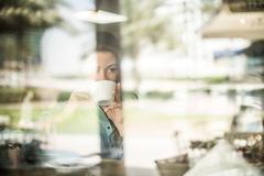 Woman drinking coffee at reflective cafe window, Dubai, United Arab Emirates Stock Photos
