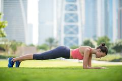 Woman doing half push ups in park, Dubai, United Arab Emirates Stock Photos