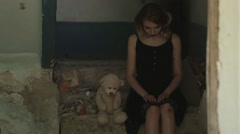 Girl sits in a destroyed room and playing with toy Stock Footage