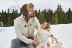 Young man wearing trapper hat petting husky in snow, Elmau, Bavaria, Germany Stock Photos