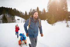 Young man pulling sons on toboggan in snow covered landscape, Elmau, Bavaria, Stock Photos