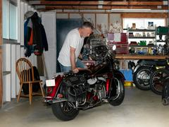 Senior man checking over motorcycle in garage Stock Photos