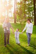 Happy young family walks in the summer park Stock Photos
