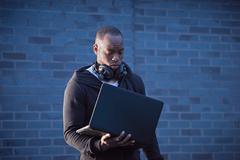 Man with headphones holding laptop Stock Photos