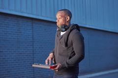 Man with headphones using handheld keyboard Stock Photos