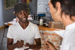 Employee in restaurant talking with chef, making notes in notebook Stock Photos