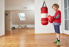 Boy with punch bag putting on boxing gloves Stock Photos