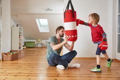 Father holding punchbag for son Stock Photos
