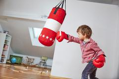 Boy wearing boxing gloves punching punch bag Stock Photos