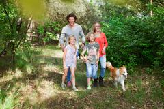 Family with dog walking together in forest Stock Photos