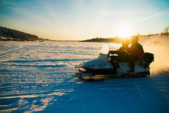 People on snowmobile on snow covered landscape Stock Photos