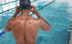 Composite image of rear view of swimmer in shirtless wearing swimminggoggle Stock Photos