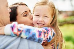 Over shoulder view of mother kissing smiling daughter on cheek Stock Photos