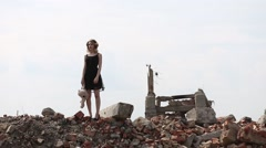girl in a black dress with a toy bear goes on destruction of buildings - stock footage