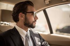Young businessman looking out from car backseat, Dubai, United Arab Emirates Stock Photos
