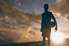 Sportsman holding a basketball against clouds - stock illustration