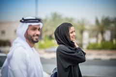 Middle eastern couple  wearing traditional clothing walking along street, Dubai, Stock Photos