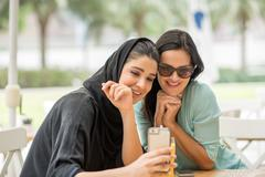 Young middle eastern woman wearing traditional clothing reading smartphone text Stock Photos