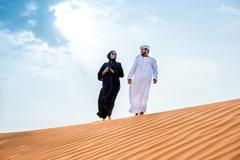 Couple wearing traditional middle eastern clothes walking on desert dune, Dubai, Kuvituskuvat