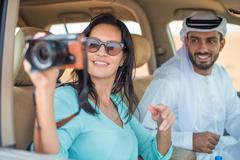 Female tourist in off road vehicle in desert taking photographs, Dubai, United Kuvituskuvat