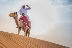 Man wearing traditional middle eastern clothes riding camel in desert, Dubai, Kuvituskuvat