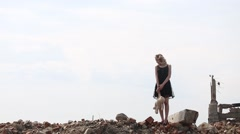 Girl in a black dress with a toy bear goes on destruction of buildings Stock Footage