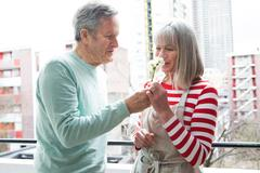 Couple smelling flower on balcony Stock Photos