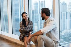Businesswoman and man sitting at window with skyscraper  view, Dubai, United Stock Photos