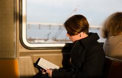 Girl reading a book in the New York subway wagon Kuvituskuvat