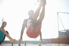 Mid adult man exercising on beach, using gymnastics parallel bars, while young Stock Photos