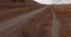 Aerial drone mountain route scene, a car and a truck driving through Stock Footage