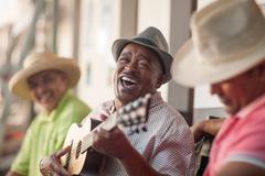 Man playing ukulele, entertaining friends Kuvituskuvat