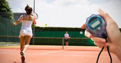 Close up of woman is holding a stopwatch against tennis match in progress - stock photo
