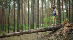 Young girl with a backpack in the woods Stock Footage