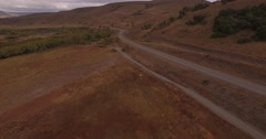 Aerial drone mountain route scene, cars passing by and the camera following a tr Stock Footage