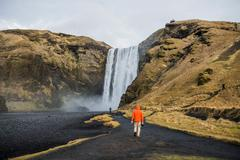 Rear view of people walking on volcanic landscape to waterfall, Skogafoss, Stock Photos