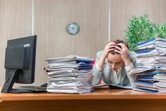 Woman under stress from excessive paper work Stock Photos