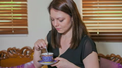 Stirring tea before drinking it Stock Footage