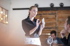 Waitress explaining to customer in restaurant Stock Photos