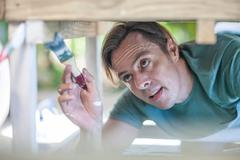 Mature man painting wooden table Stock Photos