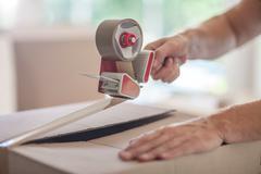 Man taping up box using tape dispenser, close-up Stock Photos