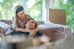 Moving house: woman sitting on bubble wrapped sofa, arms around man's neck Kuvituskuvat